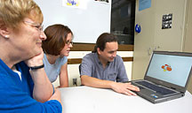 Image of researchers reviewing a laptop assessment